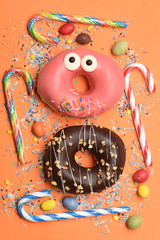 Funny glazed donuts on orange background