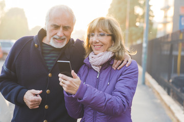 Two middle-age woman man using smart phone outdoor