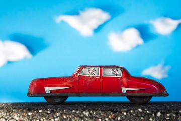 Red vintage toy car on blue background