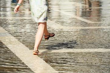 Junge attraktive Frau bei Hochwasser Aqua alta in Venedig