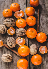 Christmas spirit: nuts, tangerines on a dark wooden background