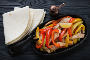 Chicken fajitas in a cast-iron frying pan and tortilla bread