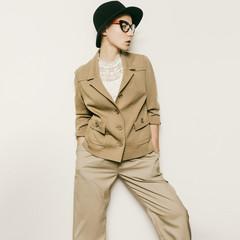 Vintage Fashion Lady. Beige classic suit and stylish eyewear. Bl
