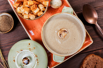 Cream soup with mushrooms, herbs, cream and crackers on plate on dark wooden background. Homemade food. Ingredients on table. Top view