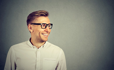 Young man with glasses smiling looking to the side
