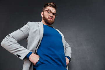 Angry bearded businessman in glasses standing with hands on hips