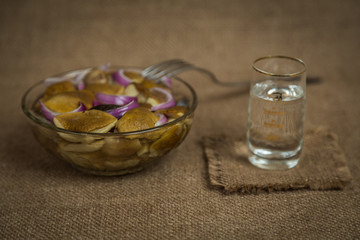 Vodka and a snack of pickled mushrooms on brown background