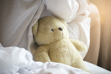 Beautiful woman with long hair wearing white pajamas,sitting on a white bed with teddy bear,in the morning.