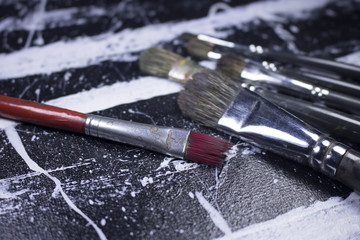 paint brush on grungy black and white acrylic paint canvas