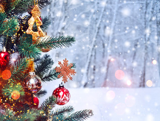 Christmas tree background and Christmas decorations with snow, blurred, sparking, glowing. Happy New Year and Xmas theme