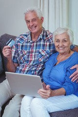 Smiling senior couple with credit card and laptop