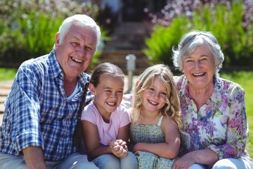 Cheerful girls with grandparents sitting in bench