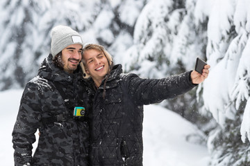 Young Man Couple Taking Selfie Photo In Snow Forest Outdoor Guys Holding Hands Winter Pine Woods