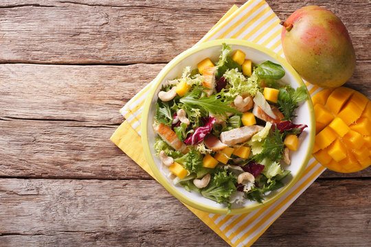 Vitamin salad with chicken fillet, mango, arugula, lettuce, spinach and chicory. horizontal top view