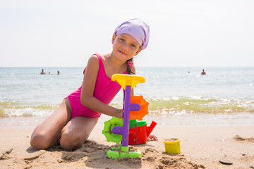 The girl in pink swimsuit playing with sand toys on the beach