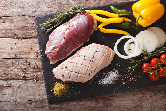 duck breast raw, with vegetables and spices close-up on a board. horizontal top view