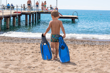 Adorable little blond kid boy having fun on tropical beach. Excited child playing and surfing in sun protected swimsuit in ocean on vacations. White sand, Kid holding flippers for swimming