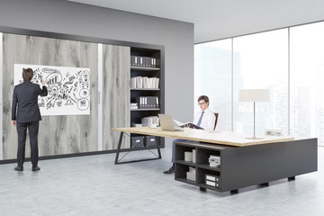 Man sitting at a massive CEO table, his colleague is drawing