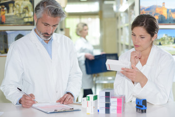 pharmacists standing at counter and showing medicine box in pharmacy