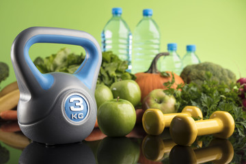 Diet and Fitness theme with healthy food. Place for typography and logo. Beautiful reflections. Bright blue background. Lots of vegetables, fruits and fitness equipment. Healthy lifestyle concept.