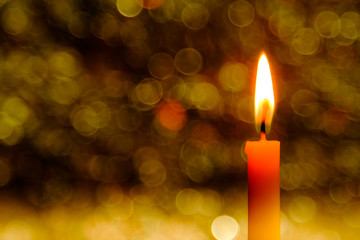 Candle flame light at night with abstract circular bokeh background Christmas lights.