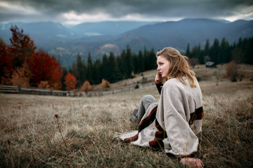 Woman in boho style. Hiker girl wrapping in warm poncho outdoor. Shot of a young woman looking at the landscape while hiking in the mountains.Outdoor shot of attractive young woman
