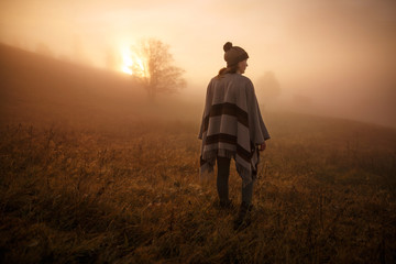 young woman hiking at mountain peak above clouds and fog Hiker girl wrapping in warm poncho outdoor.Early morning.Misty mountain.Young girl over the clouds in the valley looking at calm autumn sunrise