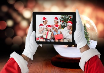 Santa claus holding a digital tablet with photo of christmas fam