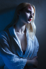 Concept: victim, accident, domestic violence. Beautiful young woman in bathrobe suffer head trauma in dramatic light.