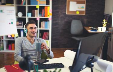 Creative businessman listening music at desk in office