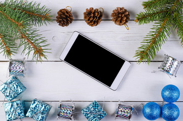Christmas decor and smartphone on a wooden background.