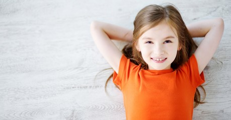 Little girl lying on white wooden floor