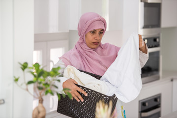 Muslim traditional woman using washing machine for laundry