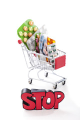 Poster Colorful drugs and pills in a shopping cart with sign STOP