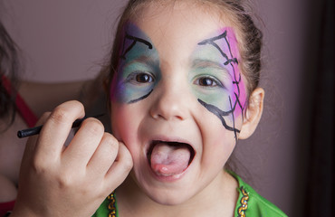 Little girl with tongue out while she is made up by make-up arti