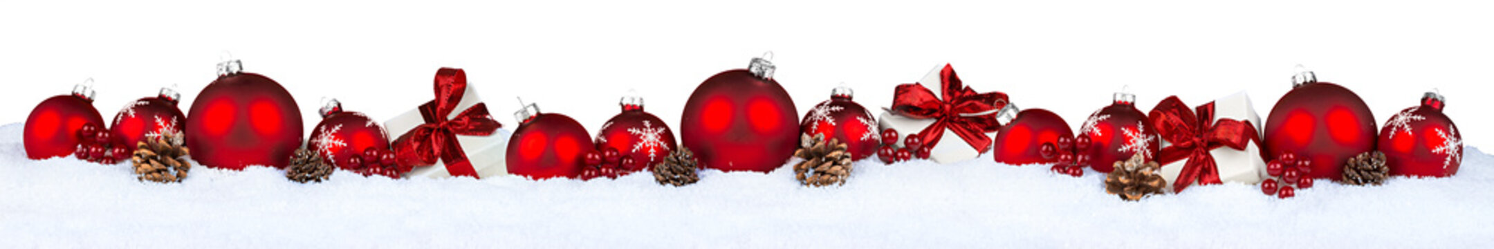 row of red christmas baubles balls in snow isolated on white background