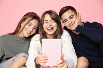 Young beautiful friends making selfie on tablet over pink background.