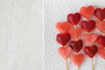 heart shape strawberry and watermelon fruit skewers on white plate