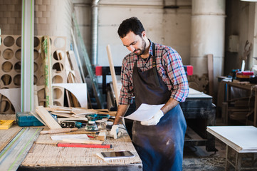 Portrait of a carpenter standing in his woodwork studio and holding notebook