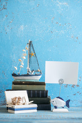 Decorative photo and marine items on wooden background.