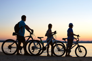 Image of sporty family on bicycles outdoors against sunset. Silh