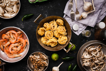 Cooking ingredients with seafood, pasta and mix chinese mushrooms. Tagliatelle pasta with chinese variety mushrooms and green vegetables. Shiitake, oyster, shimeji mushrooms.