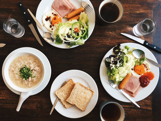 Overhead view of Hotel Breakfast - Soft boiled rice with fried eggs, bacon, sausages, ham, fresh salad, toast and hot tea on top a wooden table