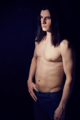 handsome young man with long hair naked torso on black backgroun