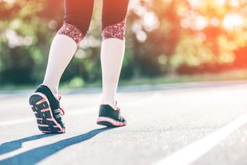 Girl Runner feet on track focus on sport shoe. Getting ready to start