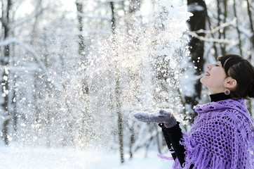 A smiling girl in in a purple shawl plays with snow outdoors, walks on a winter day in the park.