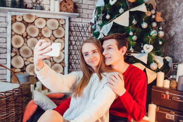 Young couple in love sitting near christmas tree having fun and make selfie. New Year