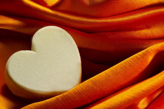Soft heart box on orange satin cloth close up