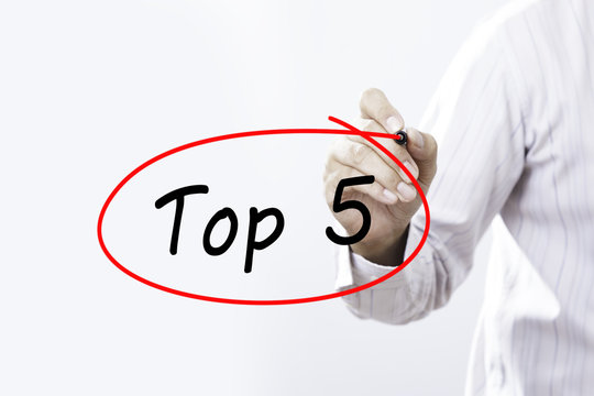 Businessman writing Top 5 with marker on transparent board. Busi