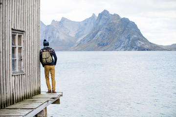 Obraz man looking at the mountains, standing on a wooden pier - fototapety do salonu